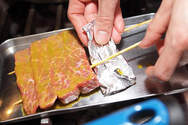 マリネ液を塗った串刺しの肉