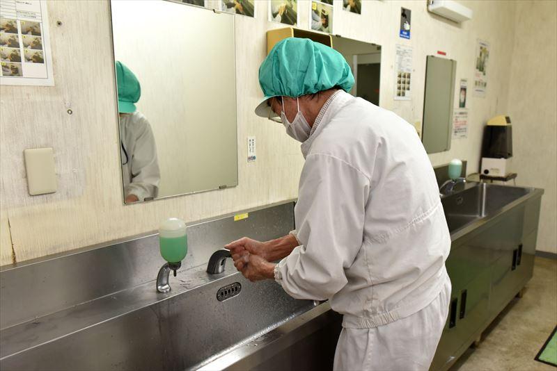 手指の洗浄・消毒中の倉持産業の折笠さん