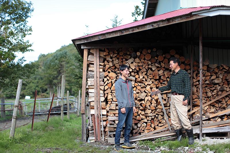 薪小屋の前にいる畑端さん親子
