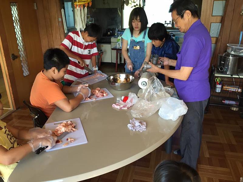 調理中の久世さんと子どもたち