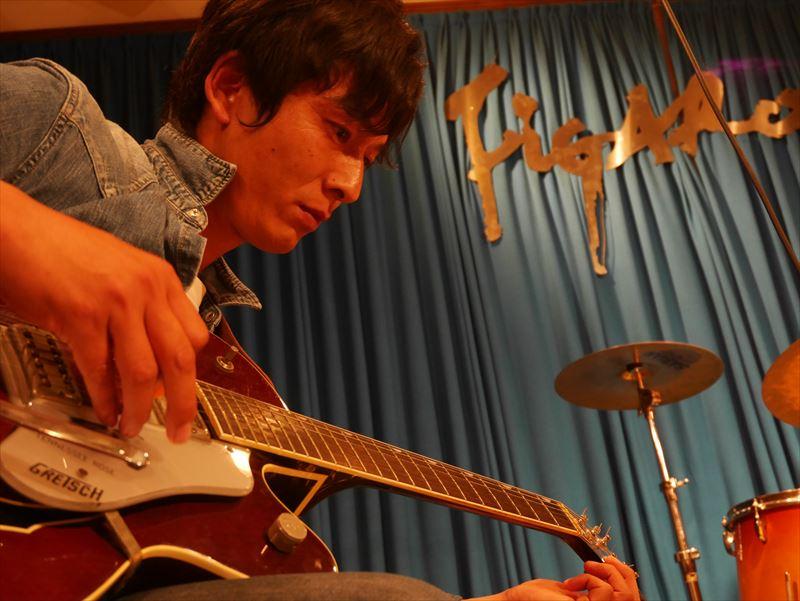 ギターをチューニングする廣澤さん