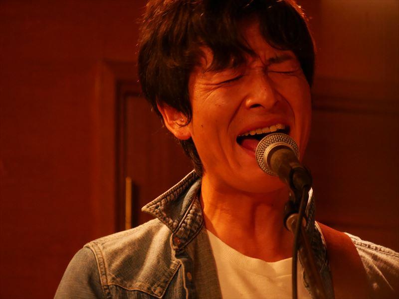 ギターを持って歌う廣澤さん