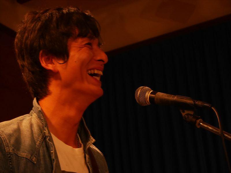 マイクの前で笑う廣澤さん